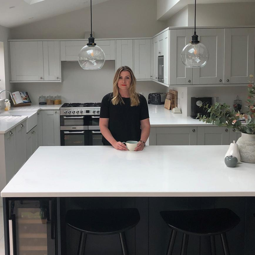 lady in black shirt standing behind navy kitchen island