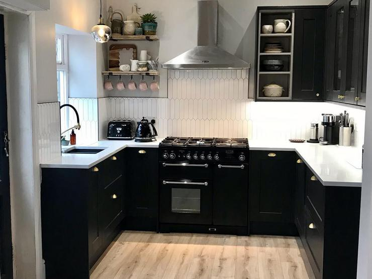 Black painted kitchen idea with shaker cupboards, pale oak floors, and white worktops.