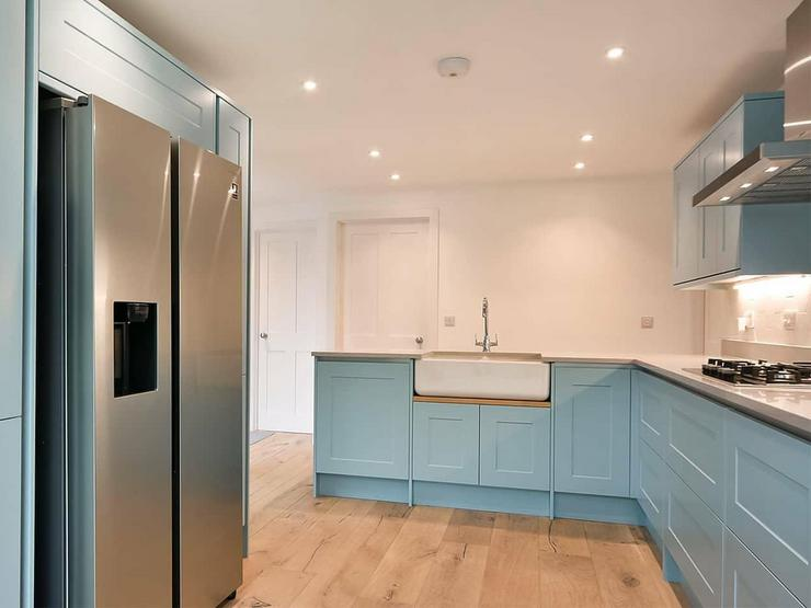 Blue painted kitchen idea using shaker cupboard doors. Includes a Belfast sink and a silver American fridge.