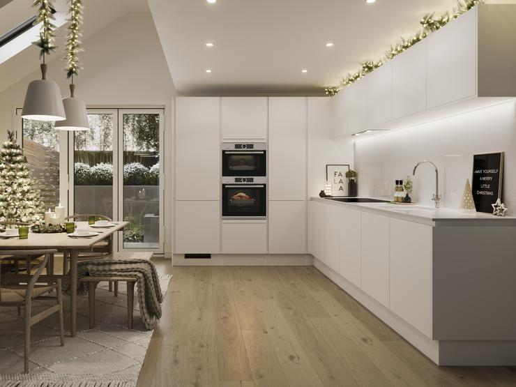 a white kitchen at christmas with a tree, fairy lights and garlands.
