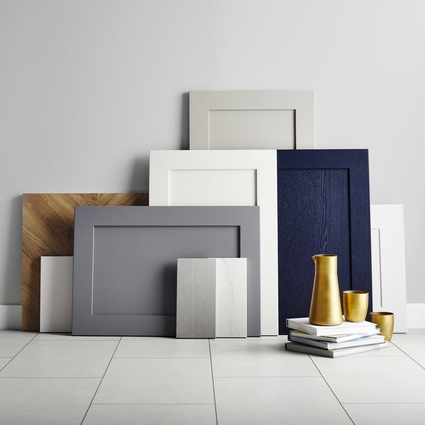 Collection of shaker doors against a wall, with white floor tiles in shot. Shown in grey, navy, and white and chevron oak.