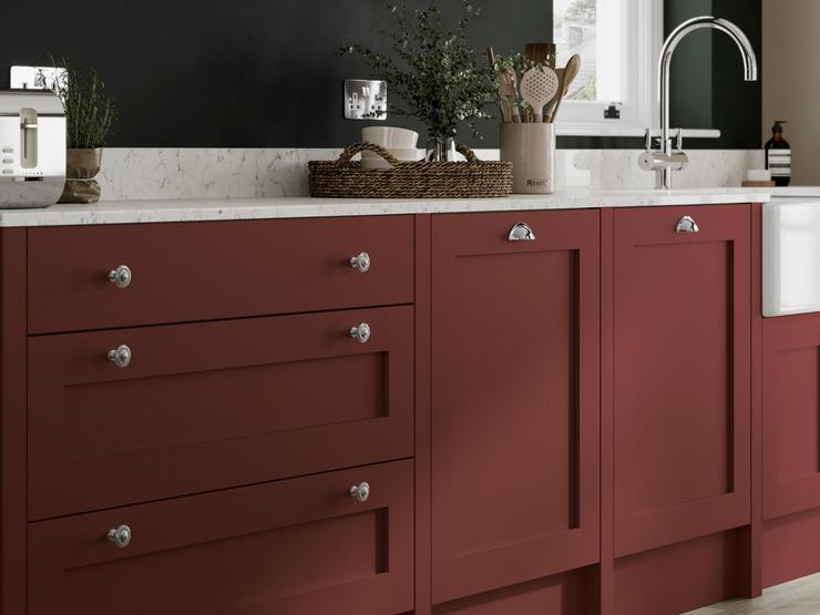 Dark red paintable kitchen idea with white quartz worktops, silver cup handles, silver tap and glass fronted wall cabinets.
