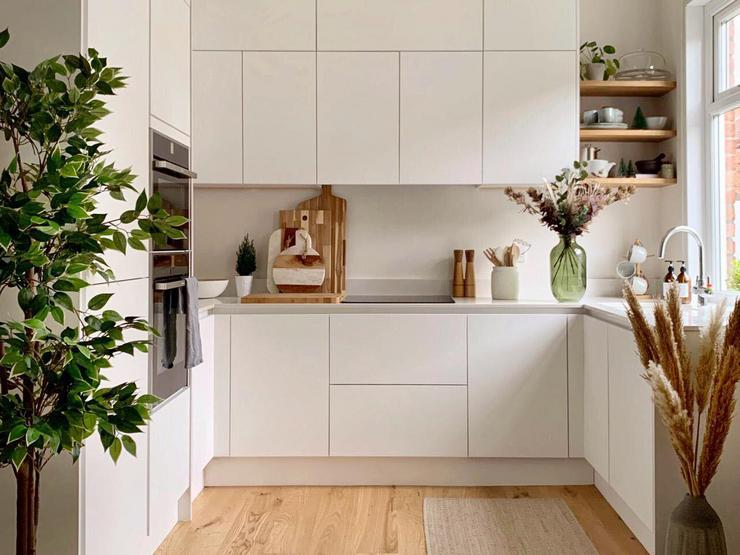 A small white kitchen makeover using matt handleless cupboards, white quartz worktops and wood flooring.
