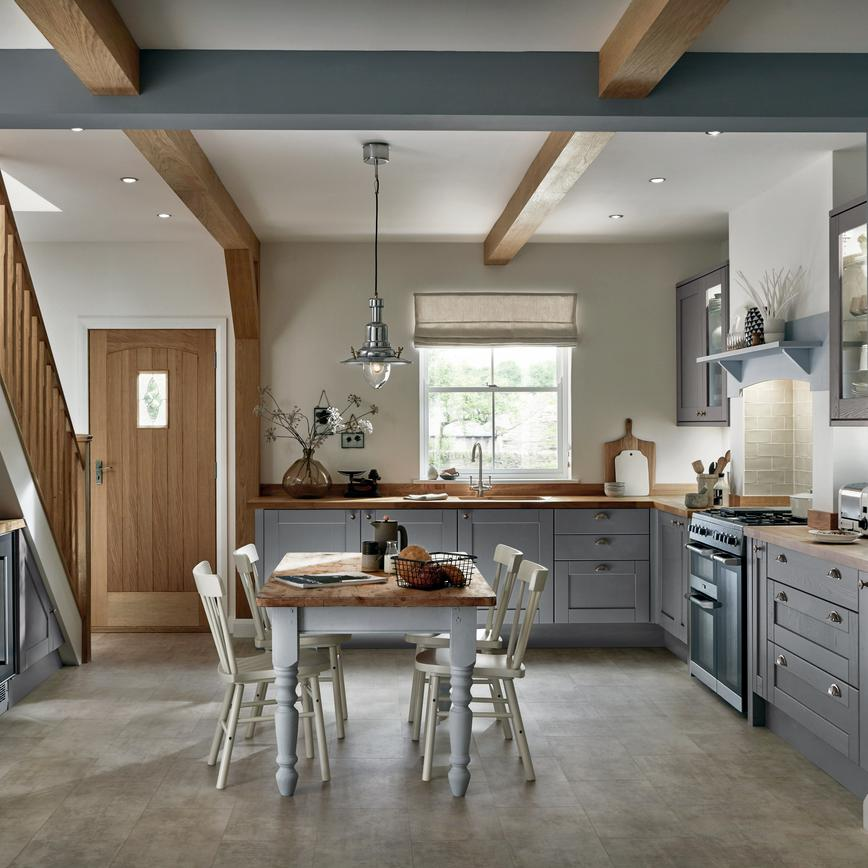 Shaker slate grey kitchen and matching under stairs storage in a cottage style design with a wood top dining table.