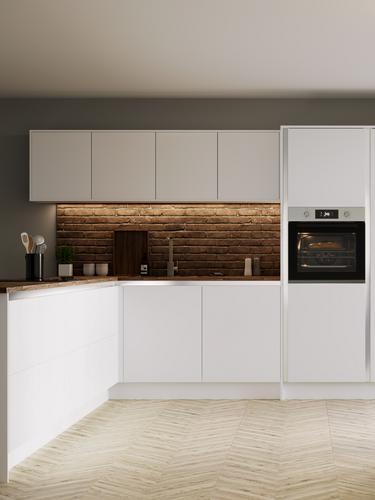 White handleless kitchen in an l shape with brick effect walls, wood worktop, chrome kitchen tap and round dining table.