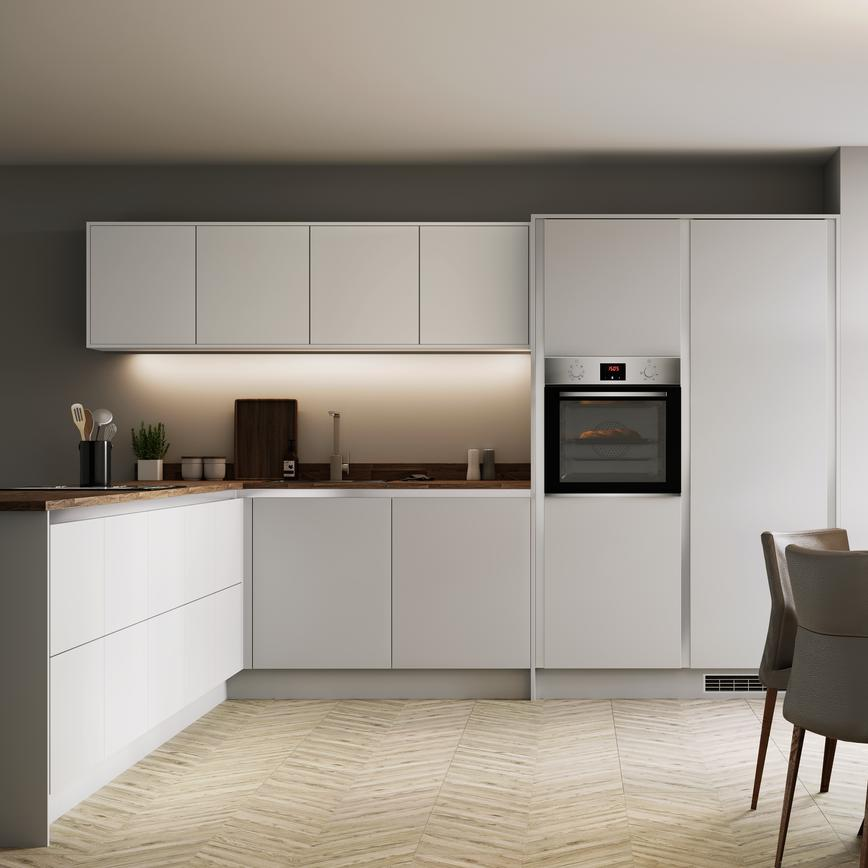 L shape dove grey handleless kitchen with single built in oven and round dining table overlooking mature garden.