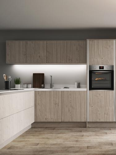 Light grey oak handleless kitchen in an l shape with wall cabinets along a single wall, white worktop and built in oven.