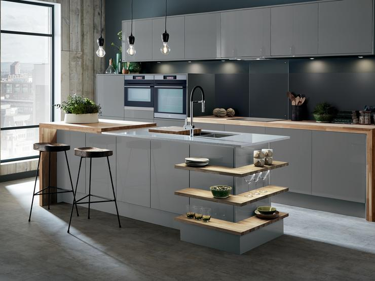 Slate grey gloss kitchen with island unit incorporating wrap around open shelves and breakfast bar with mirror chip worktop.
