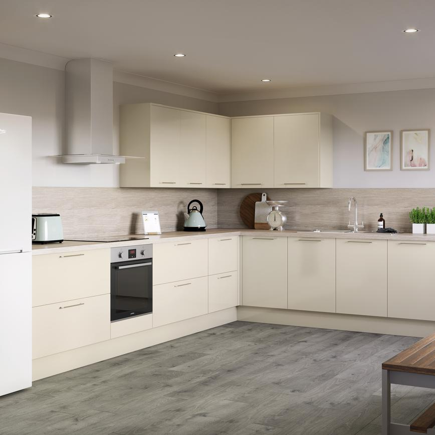 L shape kitchen in ivory with horizontal chrome bar kitchen pull handles, free standing fridge freezer and wall cabinets.