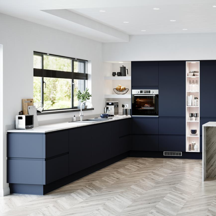 A sophisticated blue kitchen idea with integrated handle doors, white worktops, and chevron floors in a peninsular layout.