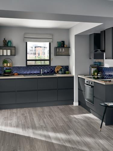 Handleless graphite grey apartment matt kitchen with wood worktop, built under oven and blue diagonal wall tiles.