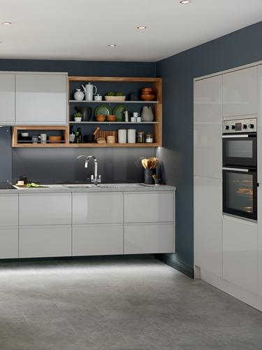 Handleless gloss grey kitchen featuring full height kitchen units set recessed into the wall with built in double oven.
