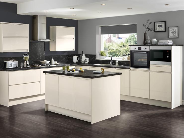Ivory white gloss kitchen and kitchen island with contrasting black marble worktop and splashback overlooking a garden.