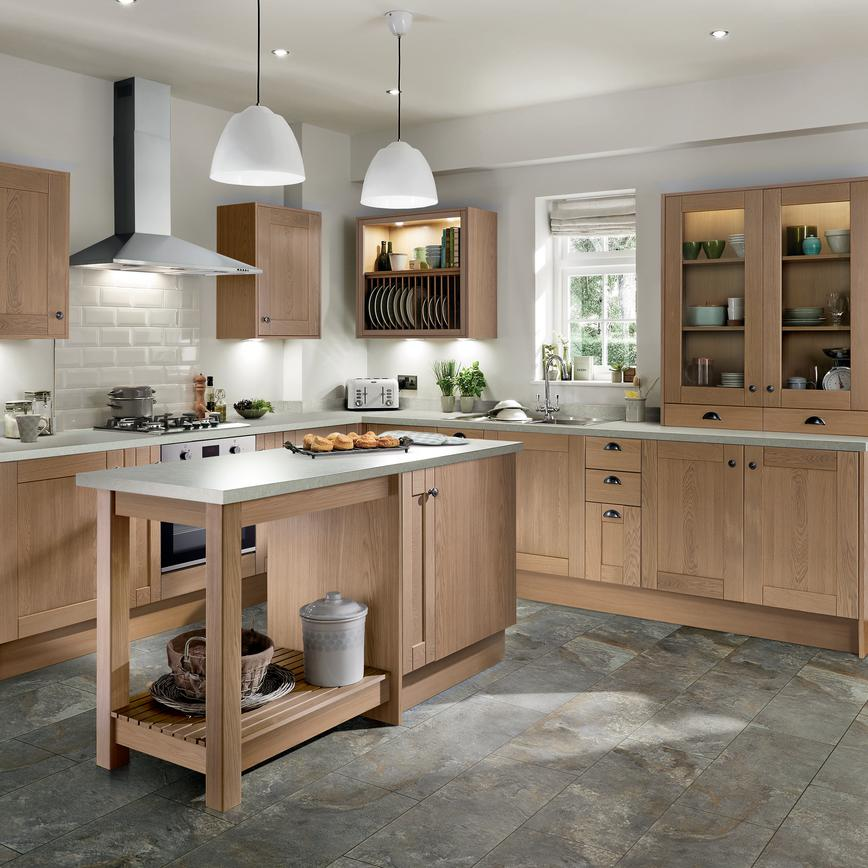 Central kitchen island with overhang surrounded by an l shaped light oak shaker style kitchen with black pull handles.