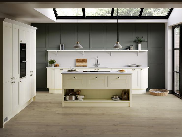 Heritage cream kitchen idea with shaker doors and chrome knob handles in an island layout. Includes green wall panelling.