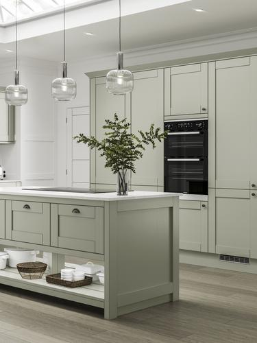 Premium timber shaker kitchen in sage green. Island unit with glass pendants over. Full height larder units and double oven.