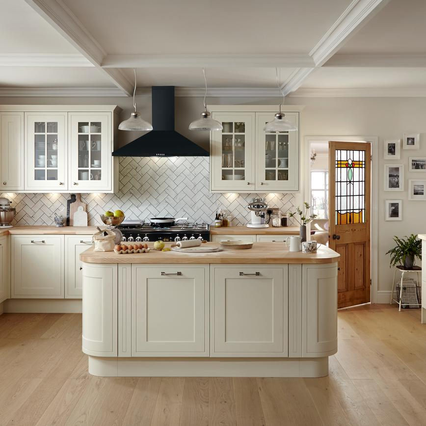 Traditional antique white framed shaker kitchen with rounded corner kitchen island unit, wood worktop and white wall tiles.