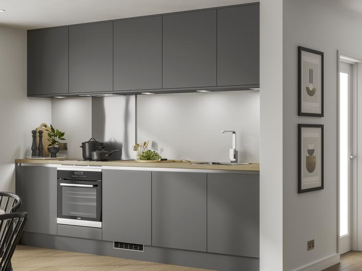 Handleless graphite grey kitchen along a single wall with built under electric oven and under cabinet led lighting.
