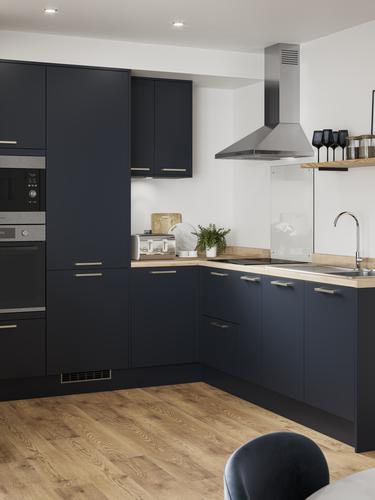 L-shaped compact kitchen layout with navy kitchen doors, wood worktops and wood flooring. Has open shelving and wall units.