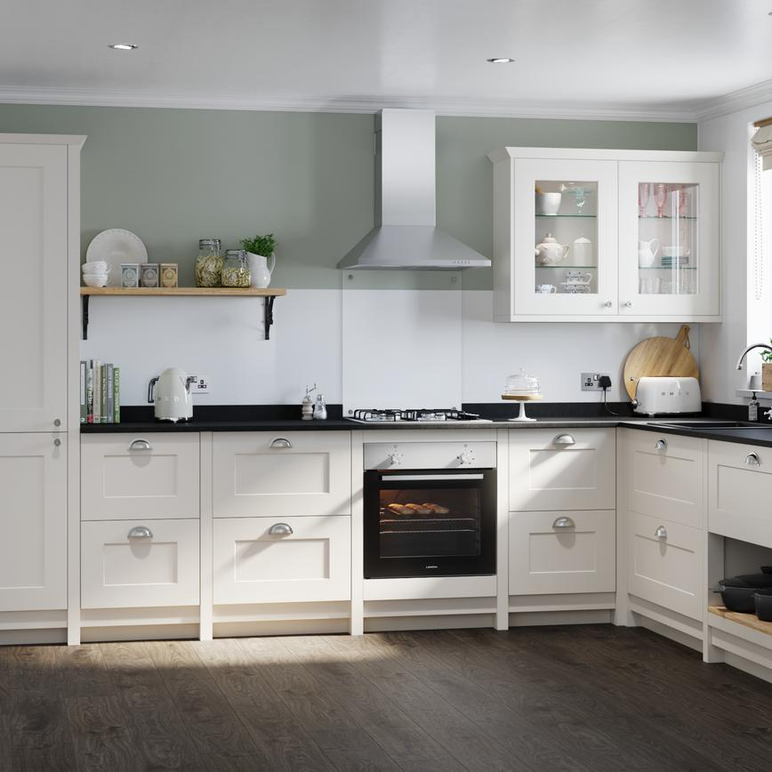 Ivory cream shaker kitchen with cup kitchen door handles in an l shape layout with built in oven, cooker hood and gas hob.