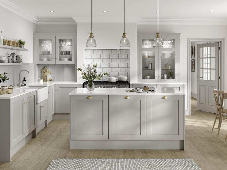Country style dove grey shaker kitchen in kitchen island layout. Recessed oven area with square white brick tiles.