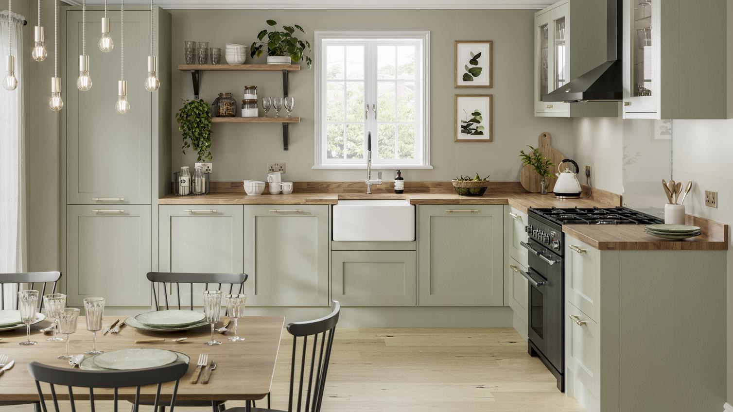 Sage green kitchen idea with shaker doors. Includes a Belfast sink, wood worktops, black extractor and black range cooker.