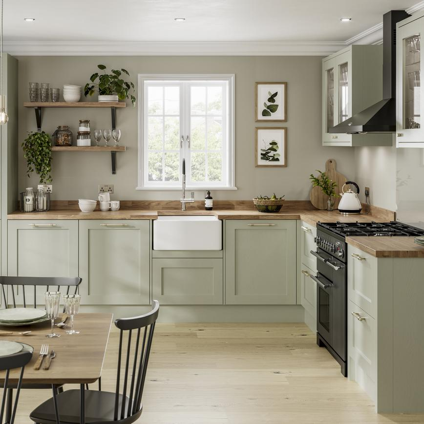 Country shaker kitchen with sage green doors. Includes a Belfast sink, wood worktops, black extractor and black range cooker.