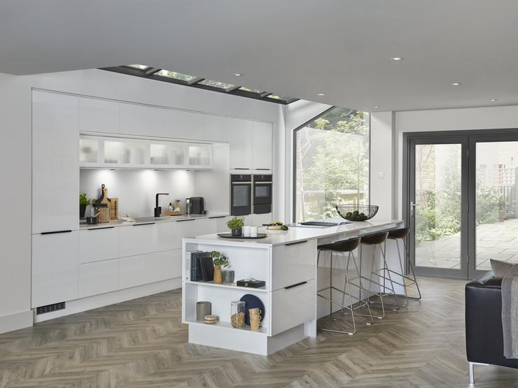 Modern white mirror gloss kitchen with two built in single oven and island unit with breakfast bar and open end shelving.