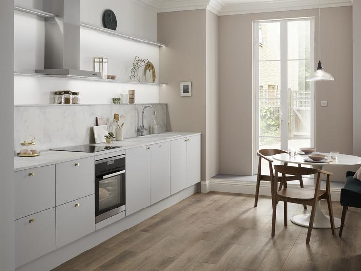 Single wall dove grey kitchen with copper knob handles, white grey marble kitchen worktop and built under oven.