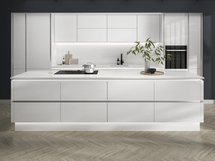 Open-plan white gloss kitchen idea with a linear design. Has white worktops and silver decorative trims for a modern feel.