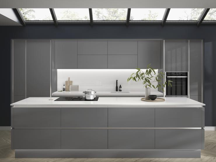 Slate grey handleless kitchen with large kitchen island, downdraft cooker hood, black kitchen tap and built in oven.