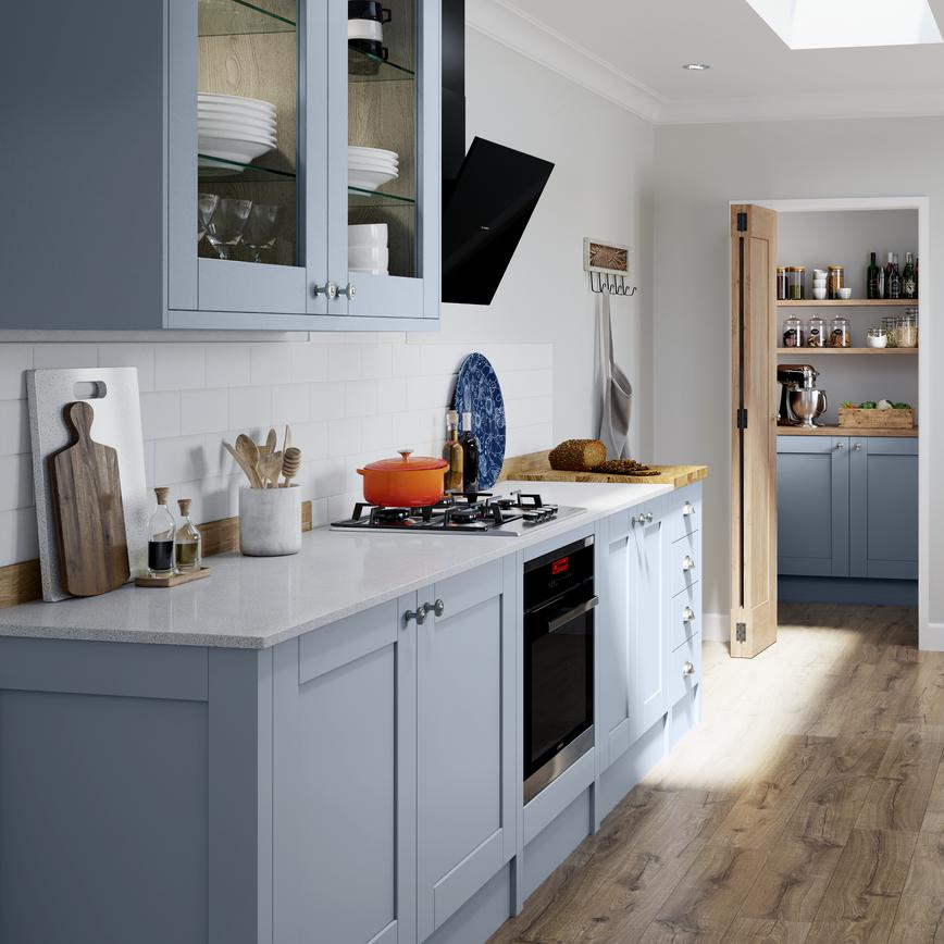 Scandinavian inspired light blue shaker kitchen in galley layout with utility room and laminate wood effect flooring.