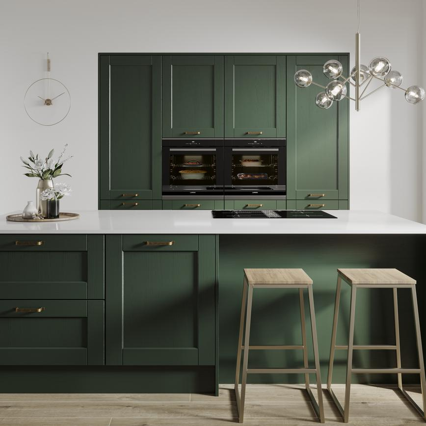 Designer green shaker kitchen with wood grain effect finish an island layout. Double larder units and two built in ovens.