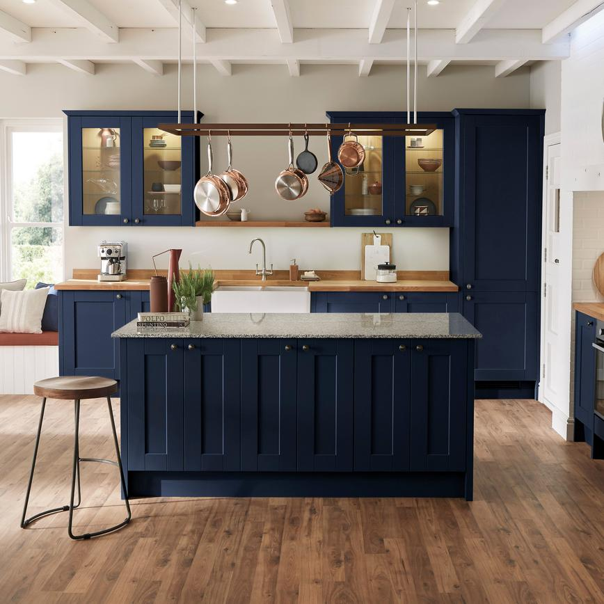 Country living styled blue navy shaker kitchen and island with traditional ceramic double belfast sink and glass cabinets.