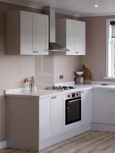 Traditional white shaker kitchen with marble worktop, built under oven and gas hob in a small L shape kitchen layout.