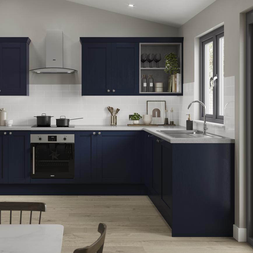 A navy kitchen in an L-shaped layout with shaker cabinets. Includes pale wood floors, grey worktops, and a chimney extractor.