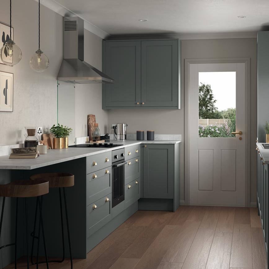 Compact grey kitchen in a galley layout. Features shaker doors, white worktops, and brass cup handles for a stately look