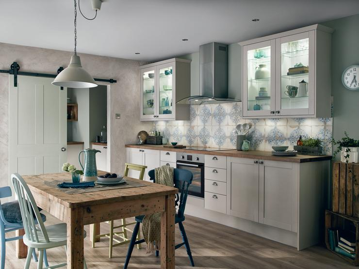 Cashmere cream shaker kitchen with blue vintage style patterned tiles, cooker hood and glass display wall cabinets.